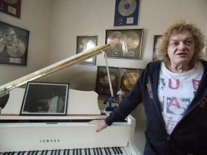 Piano Man: Robins with his gold albums and grand piano. (Photo/Local Spins)
