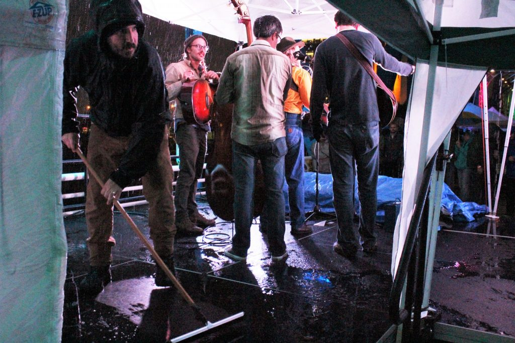 Squeegee Fest: Organizer Quinn Mathews clears water from the Blue Bridge stage on Saturday. (Photo/Anna Sink)